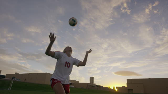 Medium slow motion panning shot of girl practicing heading soccer ball / Springville, Utah, United States