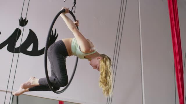 medium slow motion panning shot of girl practicing on ring in gymnasium / midvale, utah, united states - kind vor der pubertät stock-videos und b-roll-filmmaterial