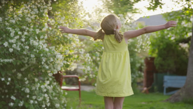 medium slow motion panning shot of girl spinning in yard / springville, utah, united states - springville utah stock-videos und b-roll-filmmaterial