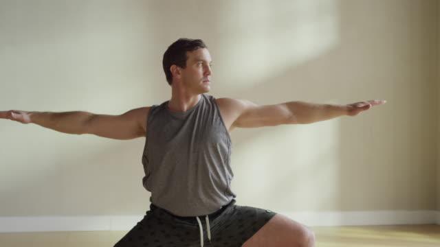 vídeos y material grabado en eventos de stock de medium slow motion panning shot of man performing warrior pose / provo, utah, united states - provo