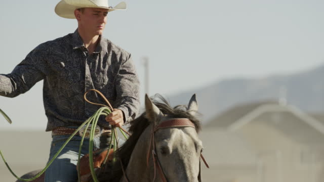 medium slow motion panning shot of man riding horse holding lasso / lehi, utah, united states - lehi stock videos & royalty-free footage