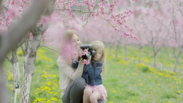 Medium slow motion panning shot of mother and daughter using camera in park / Alpine, Utah, United States