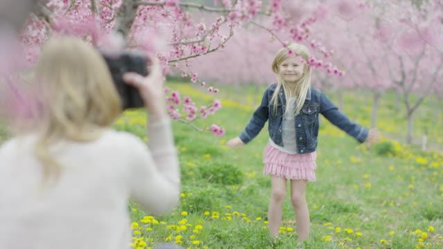 Medium slow motion panning shot of mother photographing daughter in park / Alpine, Utah, United States