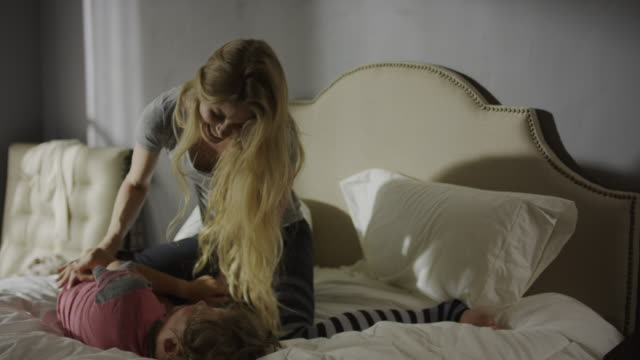 vidéos et rushes de medium slow motion panning shot of mother tickling son on bed / cedar hills, utah, united states - chatouiller