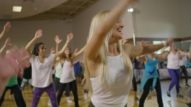 vídeos de stock, filmes e b-roll de medium slow motion panning shot of people dancing in exercise class / orem, utah, united states - outro tema
