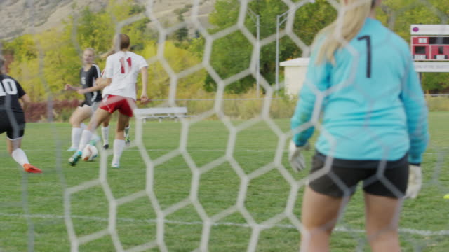 vidéos et rushes de medium slow motion panning shot of soccer match from behind net / springville, utah, united states - springville utah