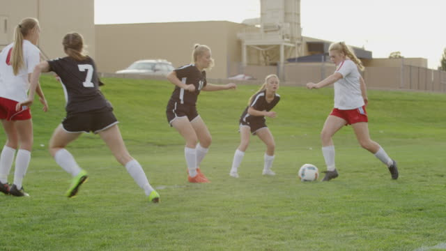 medium slow motion panning shot of soccer player scoring goal / springville, utah, united states - springville utah stock-videos und b-roll-filmmaterial