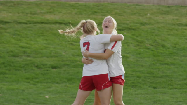 Medium slow motion panning shot of soccer team celebrating goal / Springville, Utah, United States