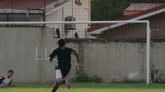 medium slow motion panning shot of soccer team celebrating score / esterillos, puntarenas, costa rica - tor konstruktion stock-videos und b-roll-filmmaterial