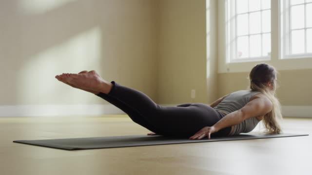 vídeos de stock e filmes b-roll de medium slow motion panning shot of woman performing locust pose / provo, utah, united states - esticar