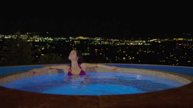 Medium slow motion panning shot of woman soaking in hot tub / Cedar Hills, Utah, United States