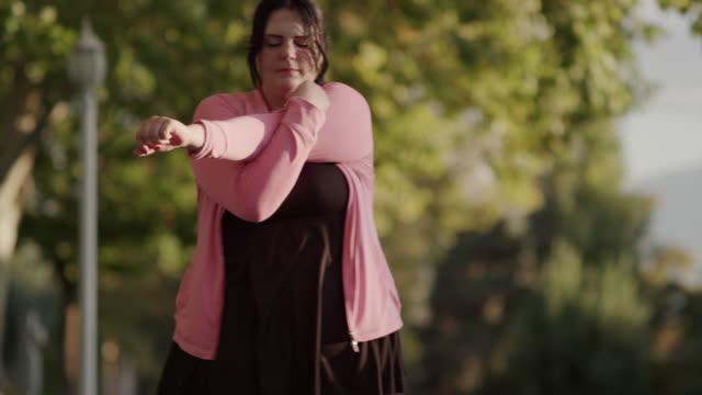 vídeos de stock, filmes e b-roll de medium slow motion panning shot of woman stretching arms on sidewalk / orem, utah, united states - orem utah