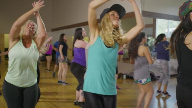 vidéos et rushes de medium slow motion panning shot of women dancing in exercise class / orem, utah, united states - autre thème