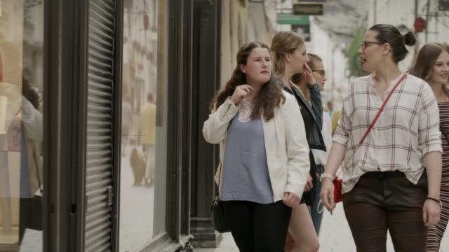 vídeos de stock, filmes e b-roll de medium slow motion panning shot of women window shopping in city / salzburg, austria - jaqueta jeans