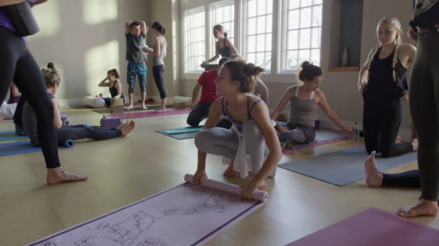 medium slow motion panning shot of yoga class ending / provo, utah, united states - nackenrolle kopfkissen stock-videos und b-roll-filmmaterial