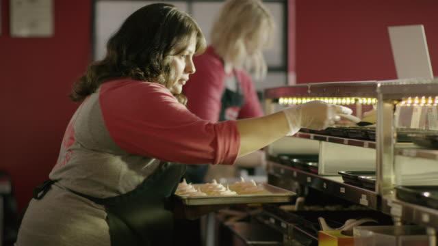 medium slow motion shot of baker placing cookies in bakery display case / salt lake city, utah, united states - skåp med glasdörrar bildbanksvideor och videomaterial från bakom kulisserna
