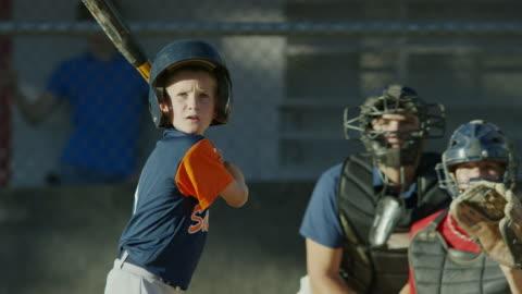 vidéos et rushes de medium slow motion shot of baseball batter swinging and missing / american fork, utah, united states - ball