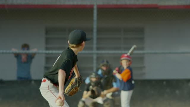 Medium slow motion shot of baseball pitcher hitting batter / American Fork, Utah, United States