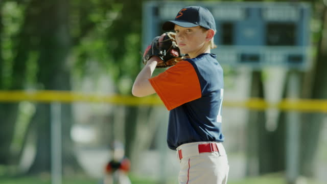 vidéos et rushes de medium slow motion shot of baseball player pitching / american fork, utah, united states - casquette de baseball