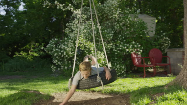 medium slow motion shot of boy smiling on tire swing / springville, utah, united states - springville utah stock-videos und b-roll-filmmaterial