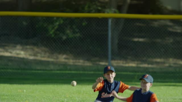 Medium slow motion shot of boys colliding in baseball game / American Fork, Utah, United States