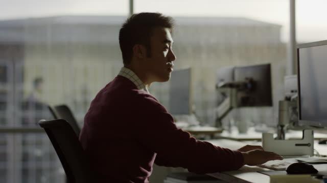 Medium slow motion shot of businessman working at desk / Lehi, Utah, United States