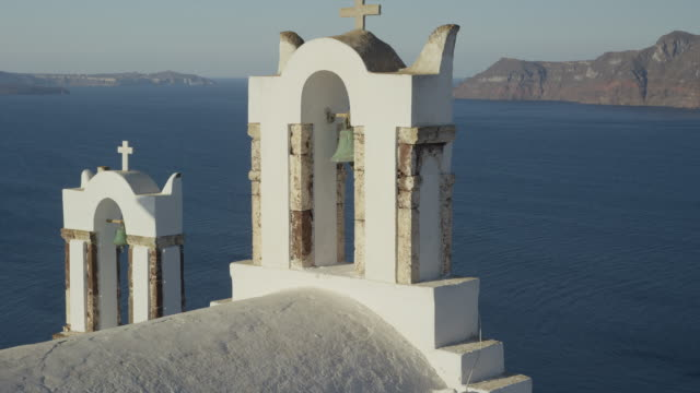 medium slow motion shot of church bell and arch overlooking ocean / oia, santorini, greece - 白しっくい塗点の映像素材/bロール