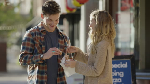 medium slow motion shot of couple on sidewalk sharing pastry / provo, utah, united states - content stock videos and b-roll footage