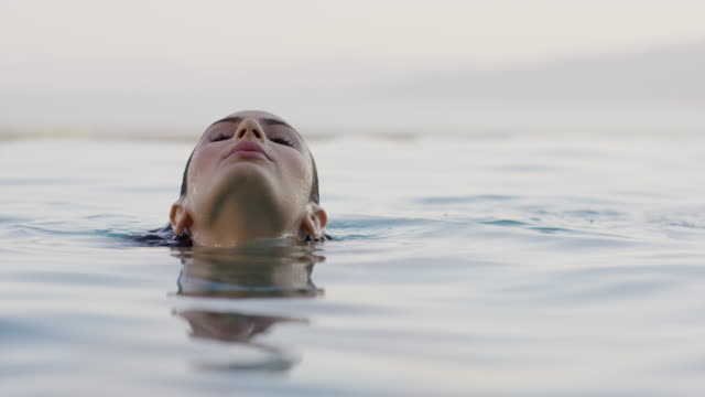 medium slow motion shot of face of woman swimming in infinity pool / cedar hills, utah, united states - infinity pool stock videos & royalty-free footage
