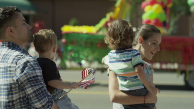 Medium slow motion shot of family watching parade / American Fork, Utah, United States