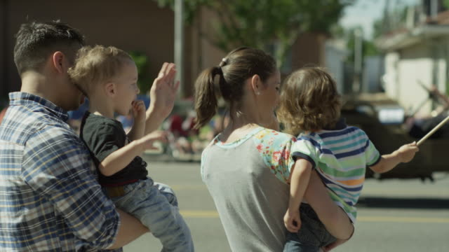 medium slow motion shot of family watching parade / american fork, utah, united states - fourth of july stock videos & royalty-free footage