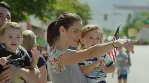stockvideo's en b-roll-footage met medium slow motion shot of family watching parade / american fork, utah, united states - optocht