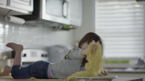 vídeos y material grabado en eventos de stock de medium slow motion shot of girl laying on counter eating spaghetti / provo, utah, united states - mischief