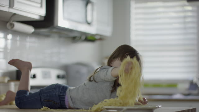vídeos de stock e filmes b-roll de medium slow motion shot of girl laying on counter eating spaghetti / provo, utah, united states - travessura