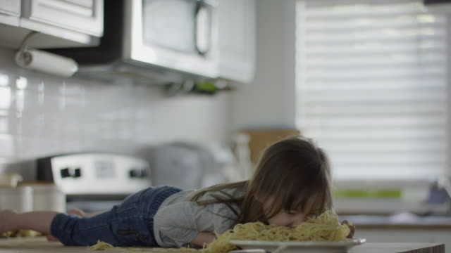 Medium slow motion shot of girl laying on counter eating spaghetti / Provo, Utah, United States