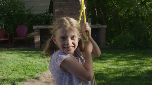 medium slow motion shot of girl looking at camera on rope swing / springville, utah, united states - springville utah stock-videos und b-roll-filmmaterial