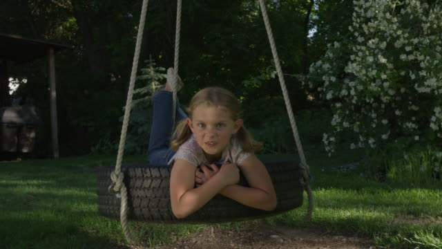 medium slow motion shot of girl making a face on tire swing / springville, utah, united states - springville utah stock-videos und b-roll-filmmaterial