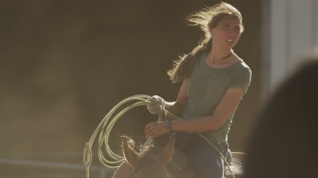 vídeos de stock, filmes e b-roll de medium slow motion shot of girl on horse holding lasso / lehi, utah, united states - lehi