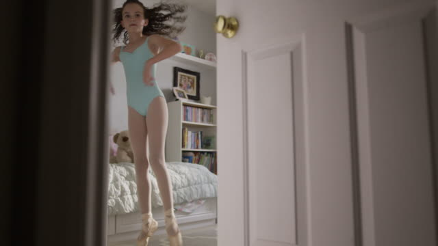 Medium slow motion shot of girl practicing ballet behind bedroom door / Provo, Utah, United States
