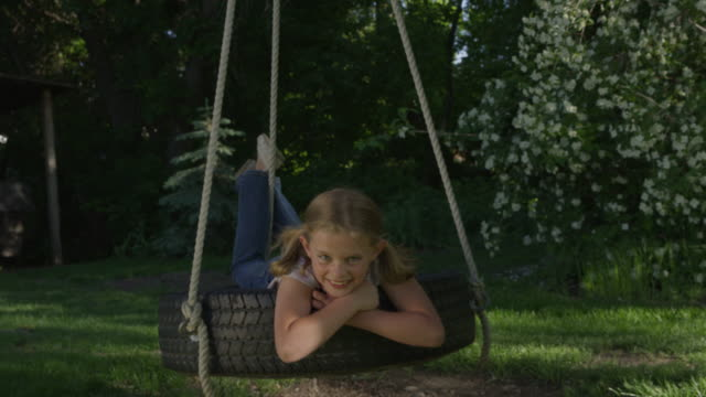 medium slow motion shot of girl smiling on tire swing / springville, utah, united states - springville utah stock-videos und b-roll-filmmaterial