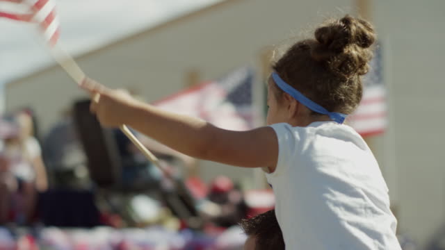 vídeos de stock, filmes e b-roll de medium slow motion shot of girl waving american flag at parade / american fork, utah, united states - bandeira norte americana