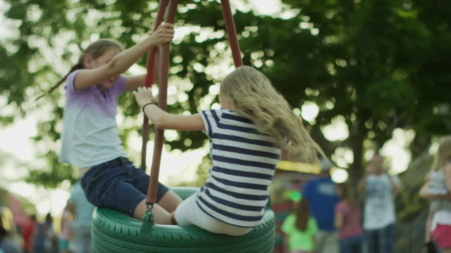 Medium slow motion shot of girls playing on tire swing / Pleasant Grove, Utah, United States