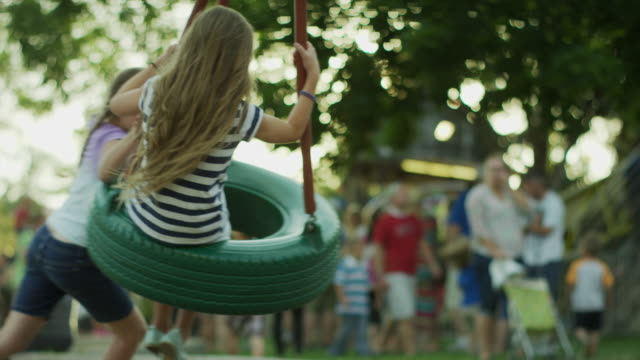 medium slow motion shot of girls playing on tire swing / pleasant grove, utah, united states - tyre swing stock videos & royalty-free footage