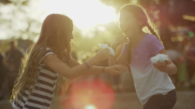 Medium slow motion shot of girls playing with cotton candy / Pleasant Grove, Utah, United States