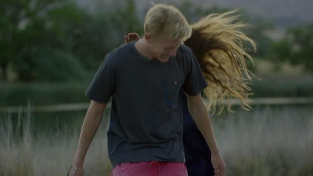 Medium slow motion shot of man carrying girlfriend piggyback / Mona, Utah, United States