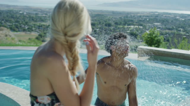 Medium slow motion shot of man shaking wet hair at woman / Cedar Hills, Utah, United States