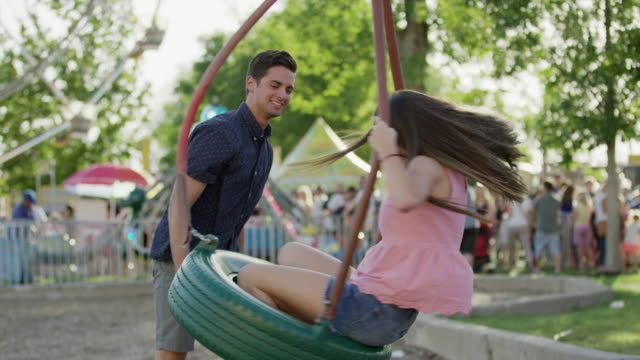 medium slow motion shot of man spinning woman on tire swing / pleasant grove, utah, united states - tire swing stock videos & royalty-free footage