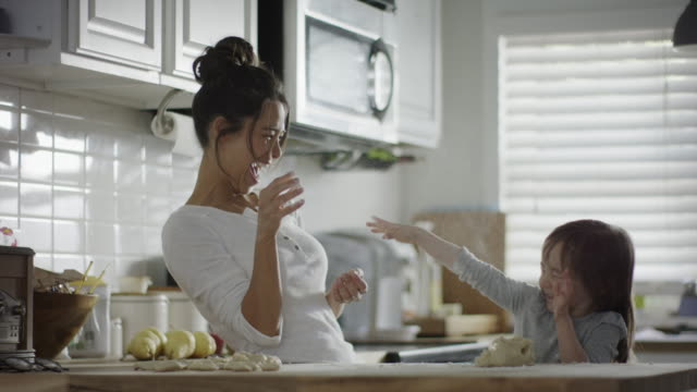 Medium slow motion shot of mother and daughter throwing flour in kitchen / Provo, Utah, United States