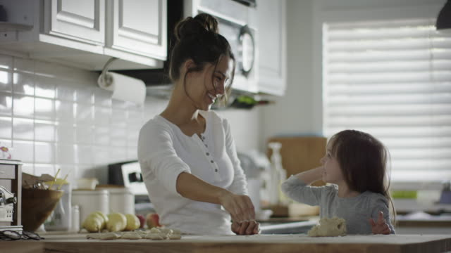 medium slow motion shot of mother and daughter throwing flour in kitchen / provo, utah, united states - provo stock videos & royalty-free footage