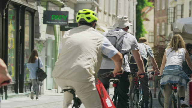 Medium slow motion shot of people riding bicycles in city / Ljubljana, Slovenia